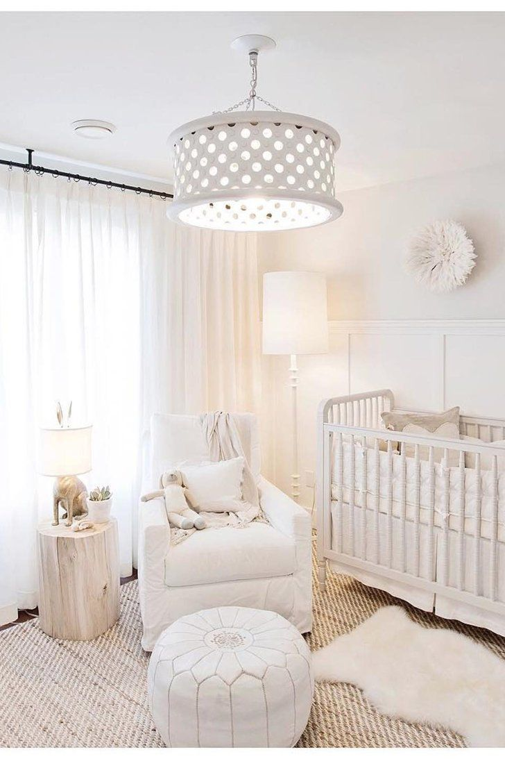 nursery, brown floor rug, white wainscoting, white wall white pendant, white crib, white chair, white round ottoman, light wooden side table, white floor lamp