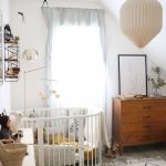Nursery, Grey Floor, White Patterned Rug, White Wall, White Round Crib, Wooden Cabinets