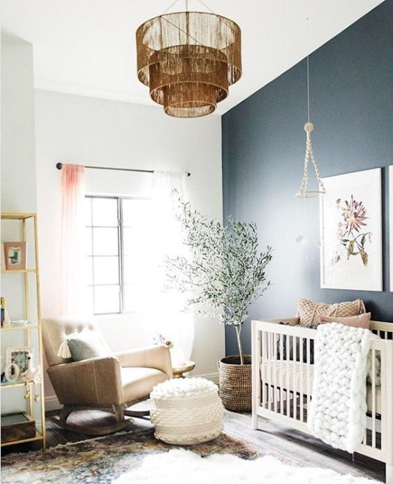 nursery, wooden floor, patterned rug, white blue wall, white crib, brown chair, white round ottoman, brown pendant