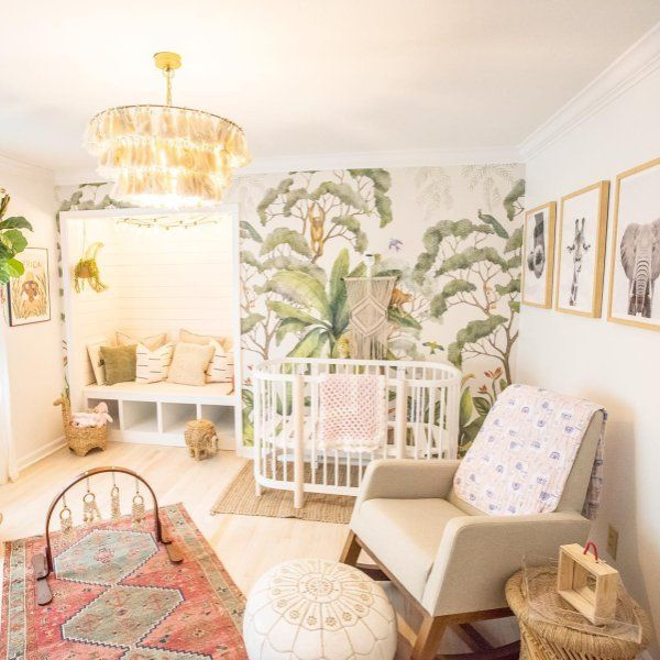 nursery, wooden floor, white built in bench in indented wall, white crib, grey chair, white round ottoman, rattan side table, pendant