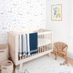 Nursery, Wooden Floor, White Wall, White Patterned Wallpaper, White Crib, Rattan Chair, Blue Fringed Chandelier
