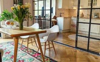 open room, wooden herringbone floor, cream wall, glass partition, white kitchen cabinet, wooden dining table, white modern chairs, patterned rug