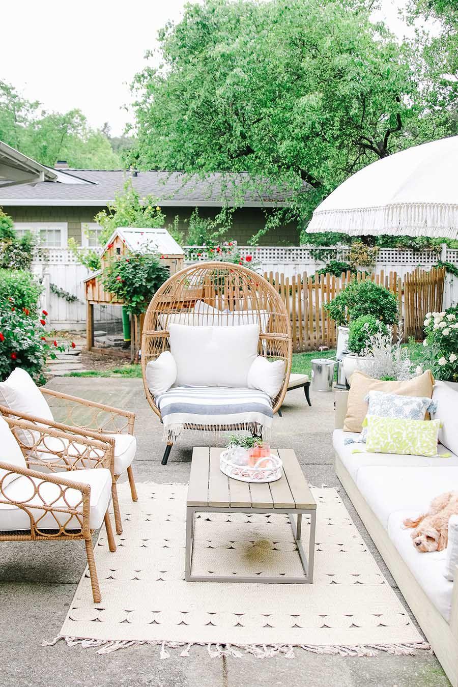 patio, grey concrete, rattan chairs, white sofa, wooden coffee table