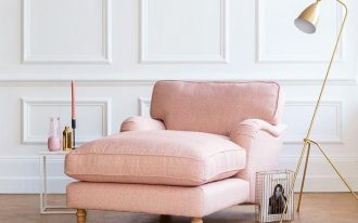 pink lounge chair, white wainscoting, wooden floor, golden floor lamp, white side table, rug