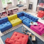 Playroom, Blue Pink Yellow Floor Sofa, Wooden Floor, White Cabinet And Shelves, White Table, Orange Square Ottoman, Dark Grey Rug