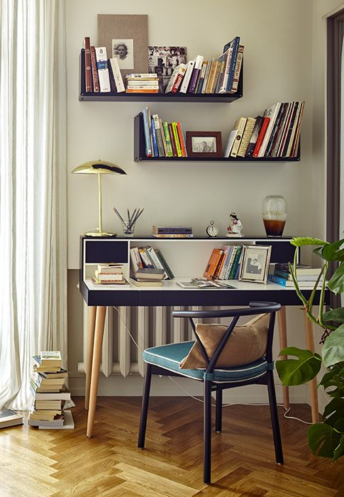small study, white wall, wooden herringbone floor, black study table, golden table lamp, black floating shelves, black chair with blue cushion