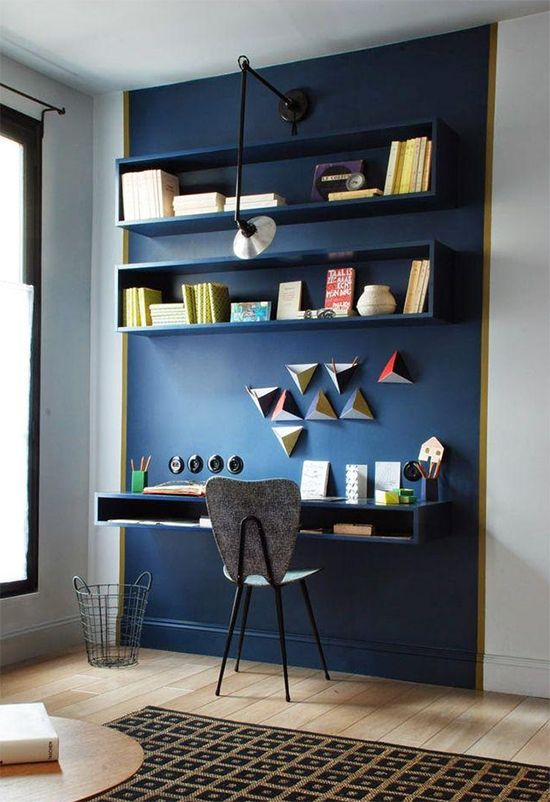 small study, wooden floor, white wall, blue accent wall, blue floating table, blue floating shelves