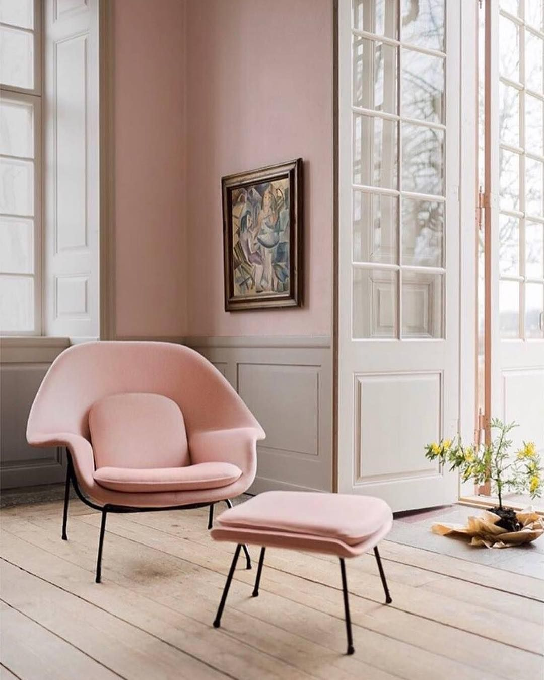 thin pink lounge chair, wooden floor, pink wall, grey wainscoting wall