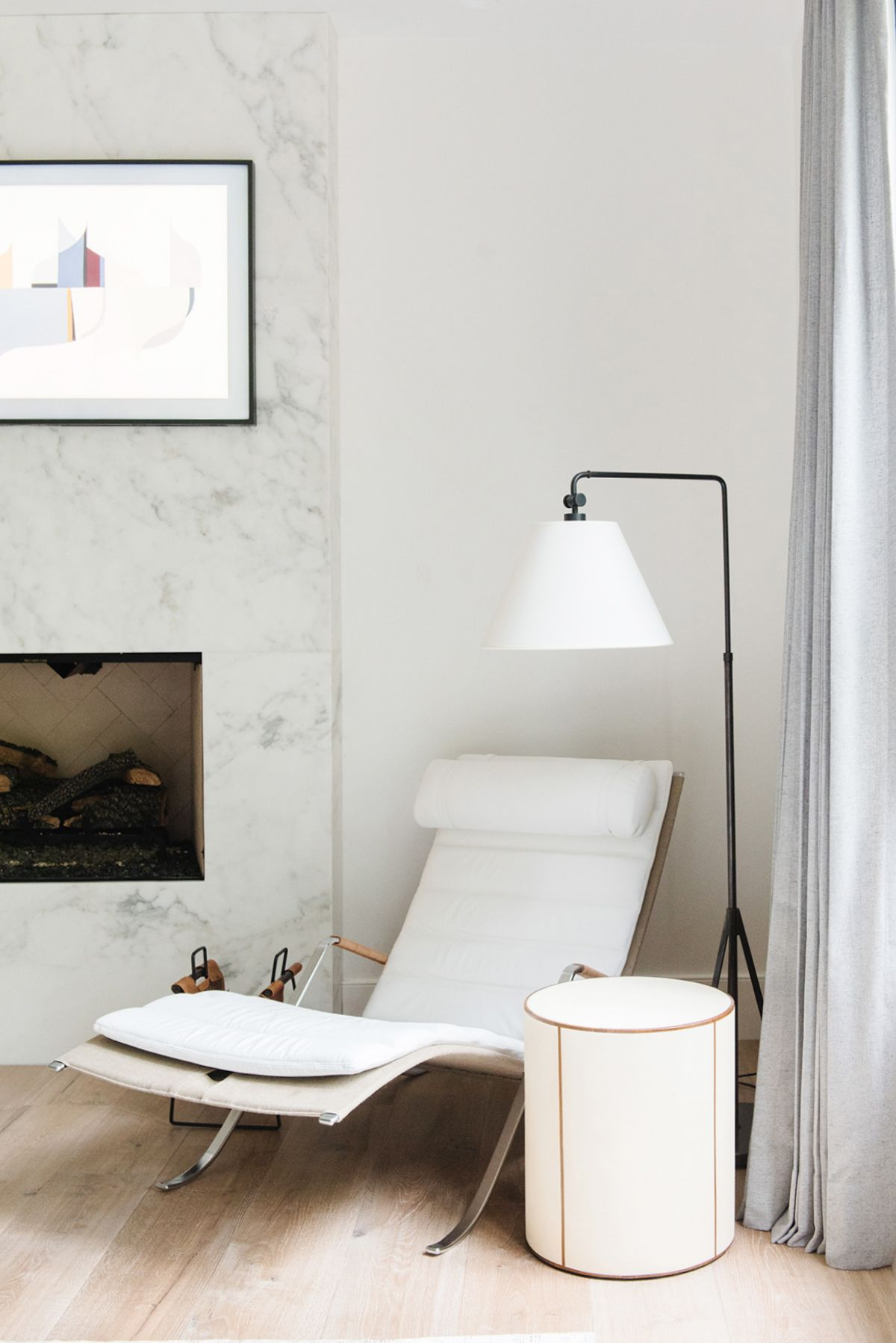 thin white lounge chair, white floor lamp, white ottoman side table, white marble accent wall