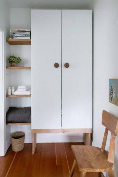 white cabinet, wooden shelves, white wall, wooden floor, wooden chair