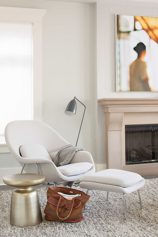 white lounge chair, white ottoman, cream wall, cream fireplace, golden side table, grey floor lamp