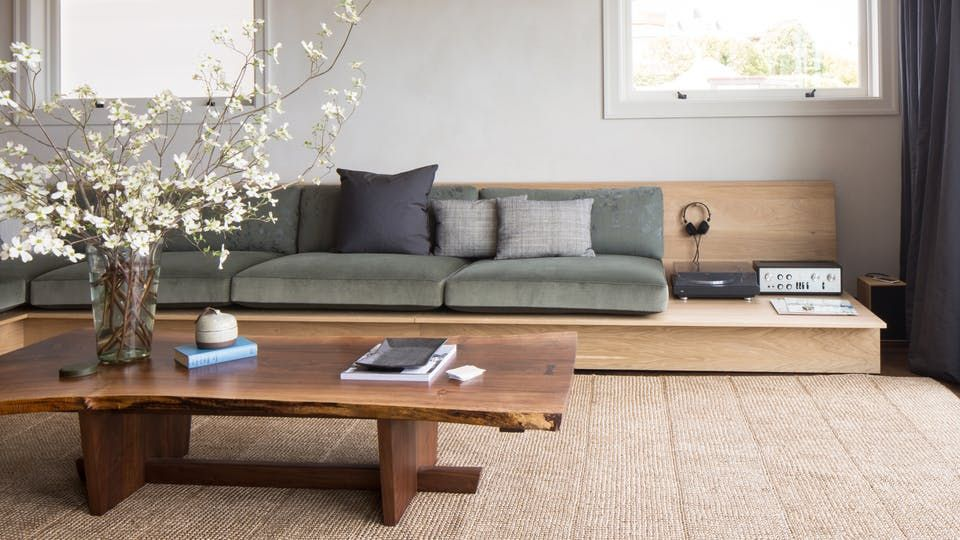 wooden bench, grey cushion, wooden coffee table, wooden floor, white wall