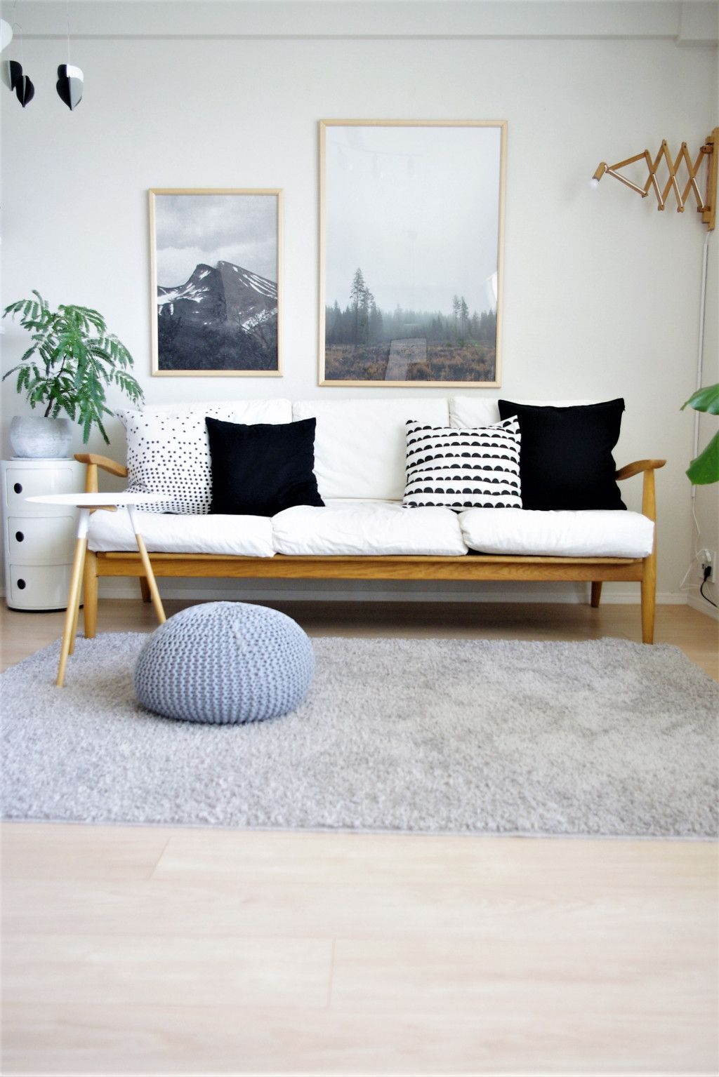wooden sofa with white cushion, wooden floor, grey rug, white wall, white side cabinget