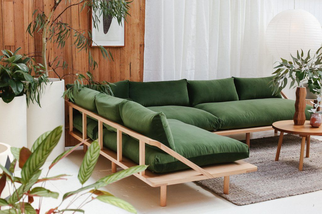 wooden thin corner bench with green cushion, white floor, grey rug, wooden coffee table, wooden wall, white curtain