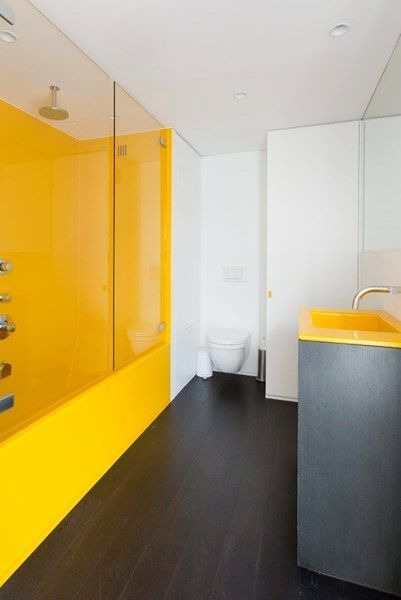 yellow bathroom, black wooden floor, white wall, yellow shower room, black rall cabinet, yellow sink, mirror