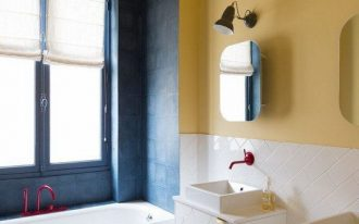 yellow bathroom, yellow patterned floor tiles, yellow wall, white wall tiles, white tiles on the tub, white cabinet with white sink, black wall