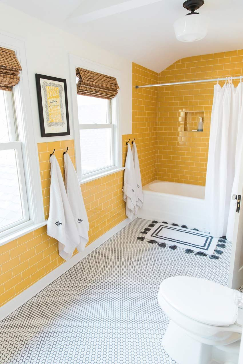 yellow bathroom, yellow subway tiles on the wall, white wall, white tiny floor tiles, white tub, white curtain, white toilet