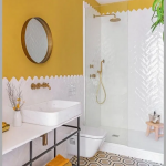 Yellow Bathroom, Yellow Wall, White Herringbone Wall Tiles, Patterned Floor Tiles, White Vanity Table, White Sink, White Toilet, Round Mirror