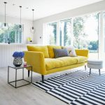Yellow Velvet Sofa, Wooden Floor, Striped Rug, Side Table, Glss Wall