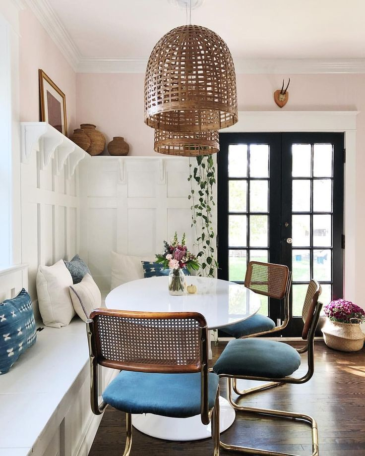 banquette, dark wooden floor, white wall, white floating shelves, white built in bench, round white table, chopper chairs with blue cushion