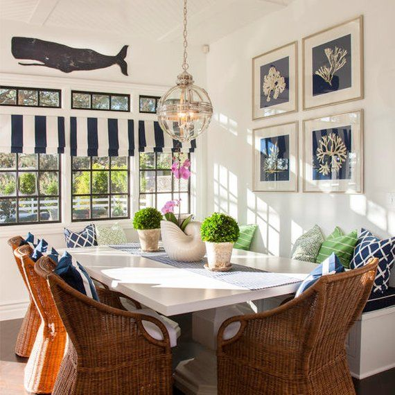 banquette, grey floor, white wall, white rectangular dining table, rattan chairs, glass pendant, white ceiling, white blue striped curtain, white corner bench