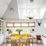 Banquette, Wooden Floor, White Vaulted Ceiling, Ceiling Windows, White Wall, White Cabinet, White Bench With Cushion, Yellow Pillows, Yellow Round Table, Wooden Chairs