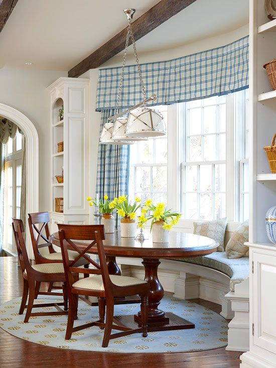 banquette, wooden floor, white wall, white shelves, white built in bench, blue cushion, wooden table, wooden chairs, white pendant