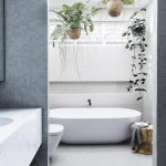 Bathrom, White Floor, White Wall, Hung Plants, White Tub, White Toilet, White Floating Vanity, Grey Tiny Tiles