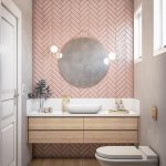Bathroom, Grey Wall, Pink Herringbone Wall, Round Mirror, Wooden Floating Vanity With White Top, White Sink, Golden Faucet