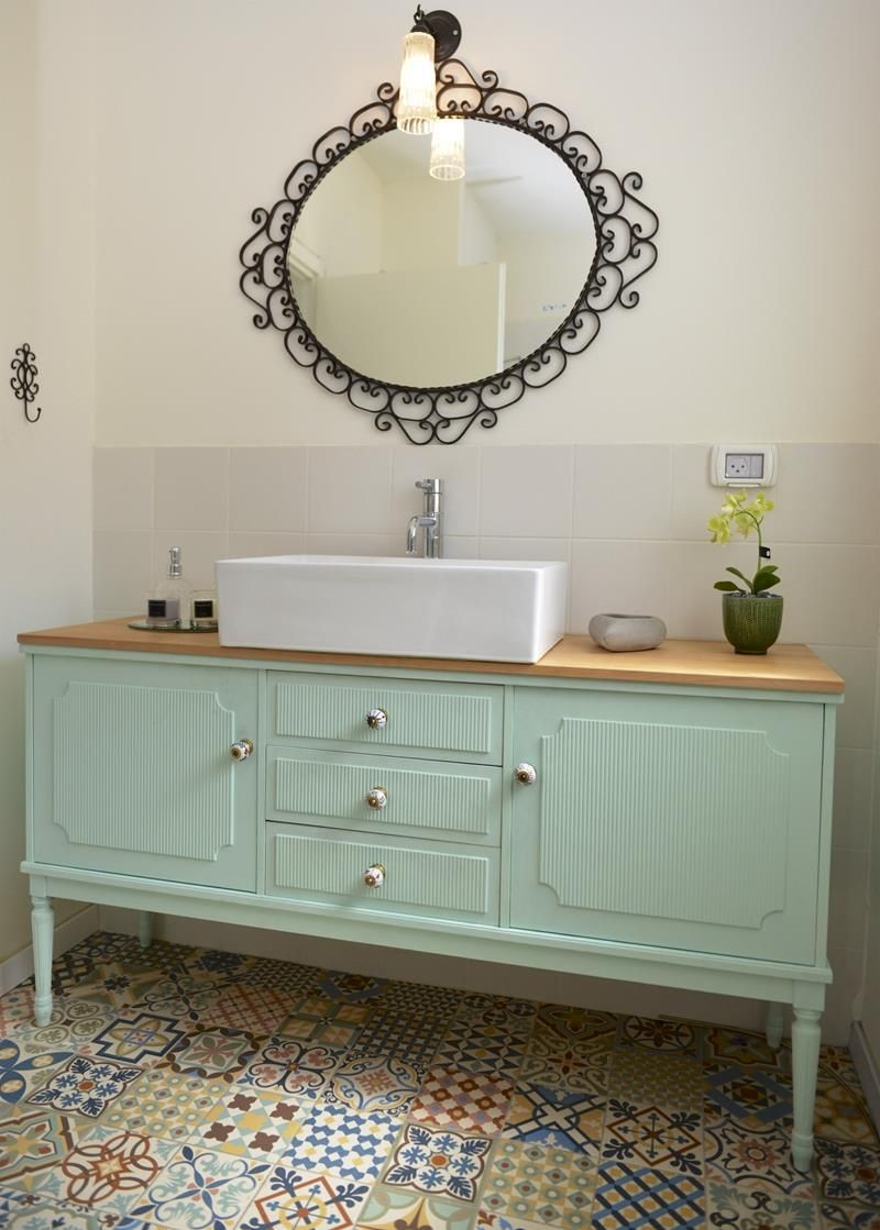 bathroom, patterned floor tiles, white wall, white wall tiles, green wooden cabinet, wooden top, white sink, round mirror with black metal frame