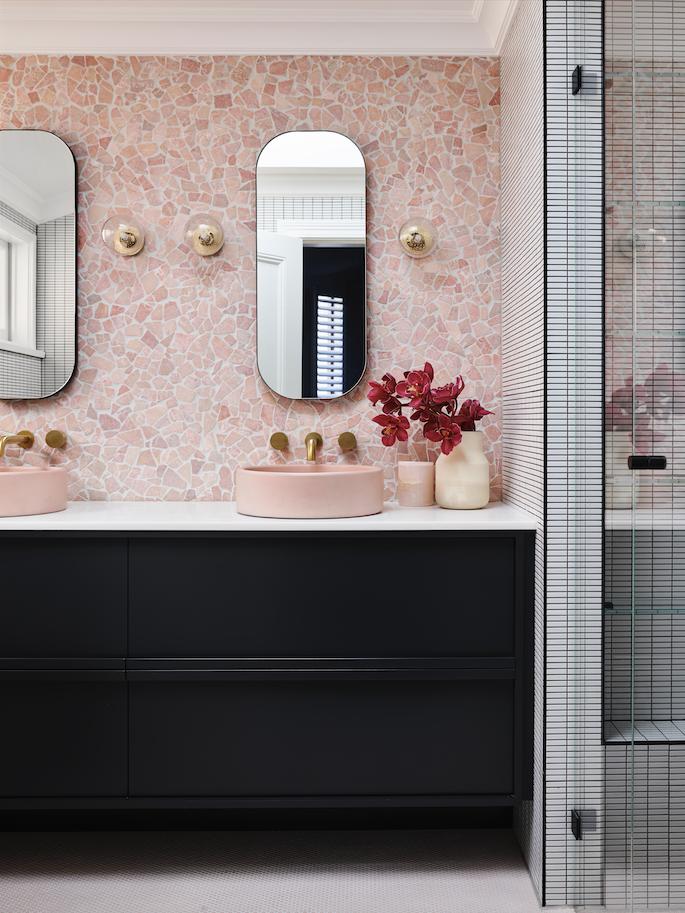 bathroom vanity, pink backsplash, black cabinet with white top, pink round sink, golden faucet, mirror