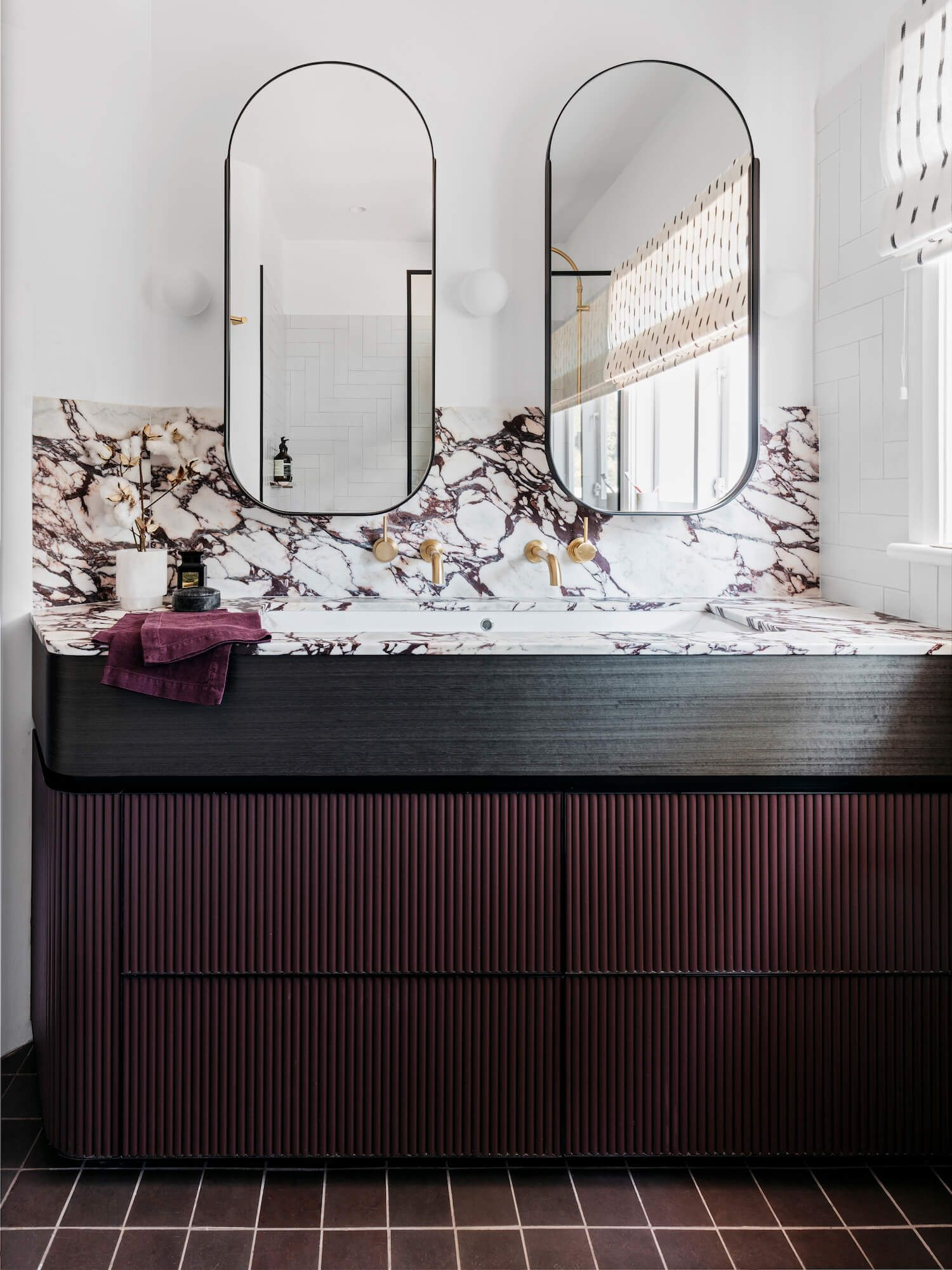 bathroom, white wall, black floor tiles, white marble top and bakcsplash, black lines, dark cabinet