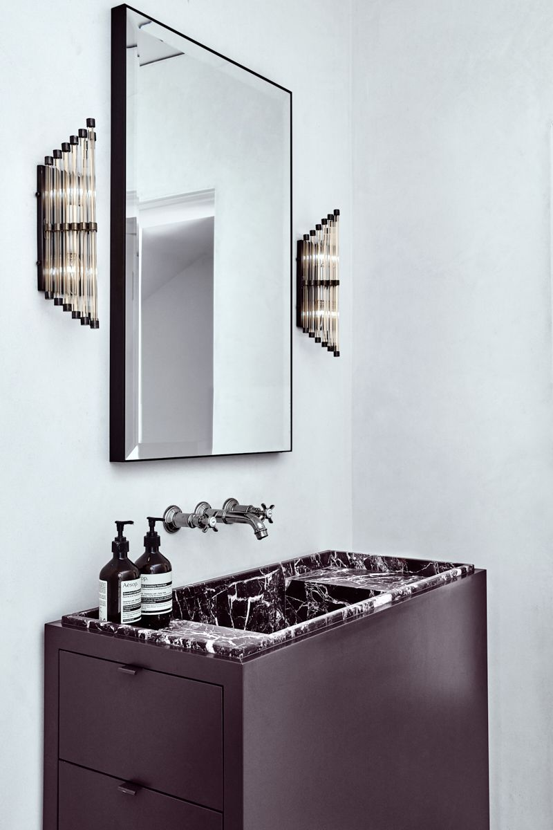 bathroom, white wall, black vanity cabinet, black marble top, mirror, sconces