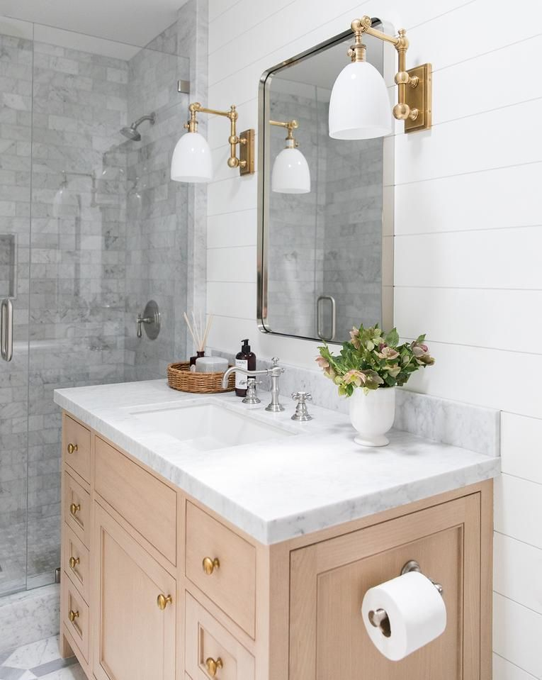 bathroom, white wooden wall, wooden vanity cabinet, white marble top, mirror, sconces with golden line and white cover