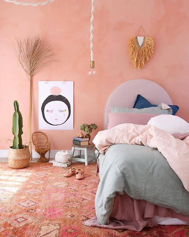bedroom, pink patterned rug, peach pink wall, pink headboard, pendant