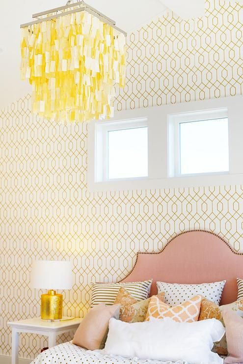 bedroom, white patterned wal, pink headboard, pillows, white side table, golden table lamp with white cover, yellow white chandelier
