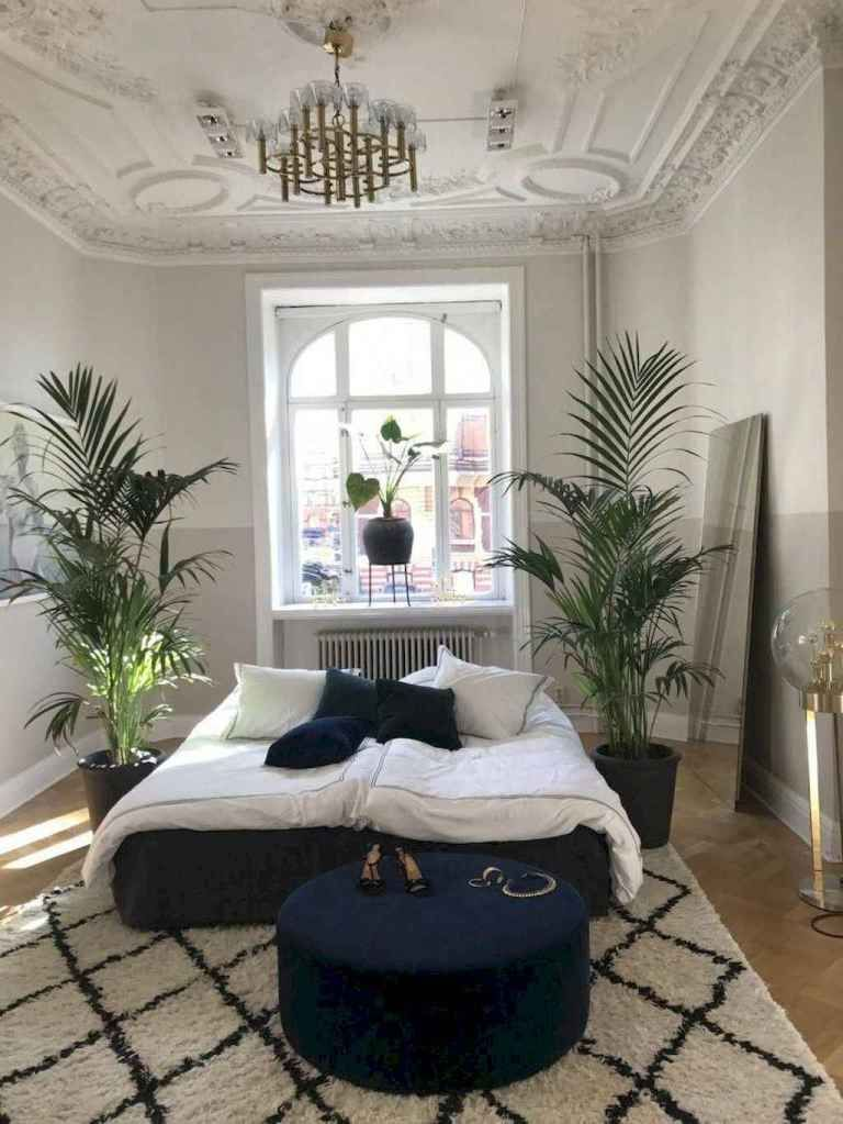 bedroom, wooden floor, patterned rug, blue velvet round ottoman, blue velvet bed platform, white wall, white carved accent ceiling, chandelier