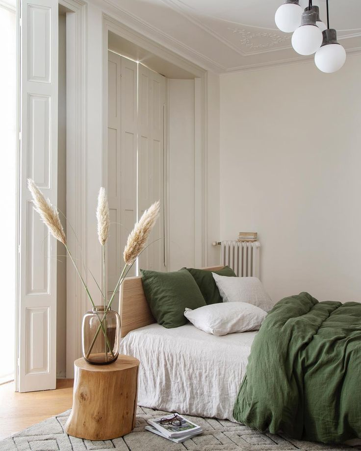 bedroom, wooden floor, patterned rug, white wall, wooden bed platform, white bed, wooden side table