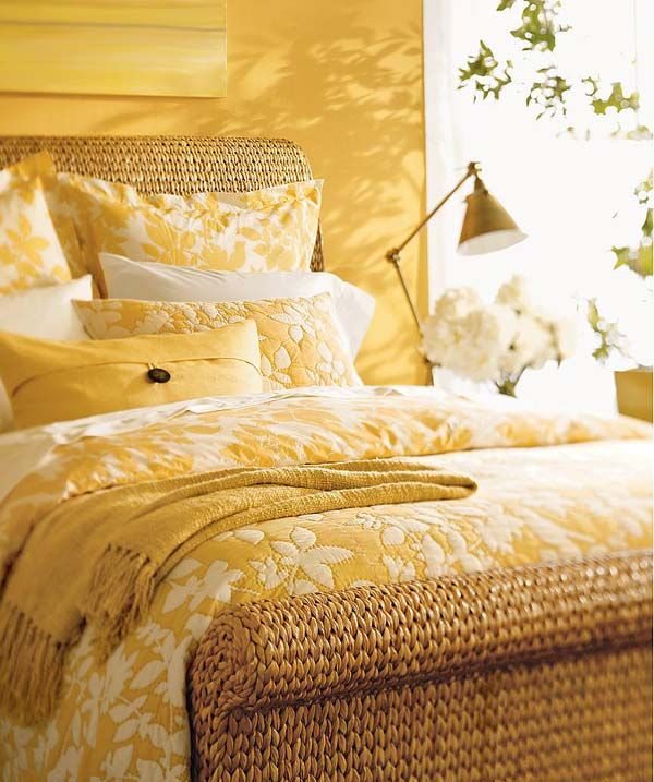 bedroom, yellow wall, rattan platform, yellow bedding, yellow table lamp