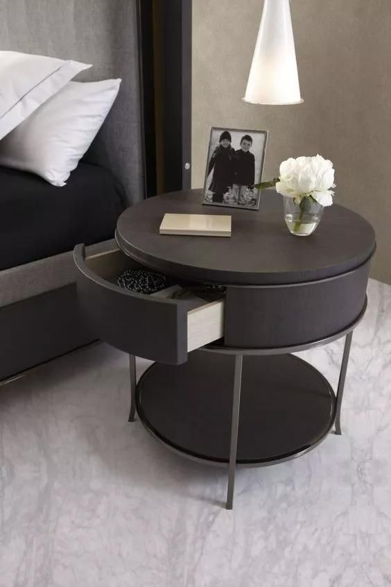 black round table with drawers on top and shelf on the bottom