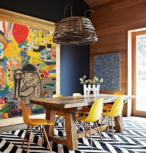 dining room, black white chevron rug, wooden table, yellow modern chairs, wooden wall, colorful painting,