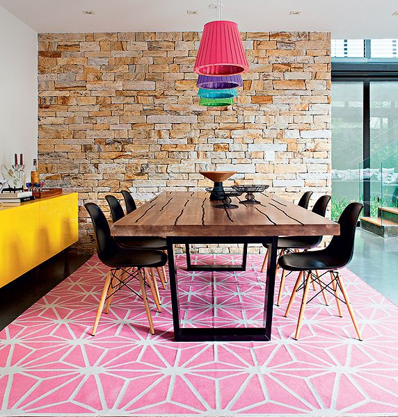 dining room, pink pattern rug, white wall, yellow cabinet, wooden table, black modern chairs, exposed wall, red purple blue green pendants