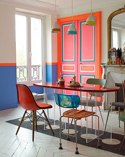 dining room, white chevron floor tiles, white blue wall, oval dining table, chairs, grey rug, pink door, red blue yellow pendants
