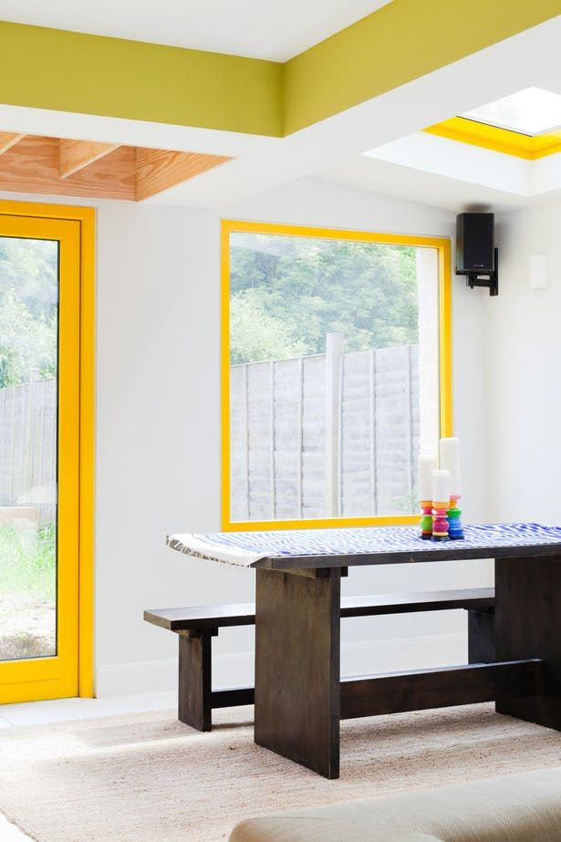 dining room, white floor, white wall, yellow window frame, wooden dining table and bench, yellow door frame
