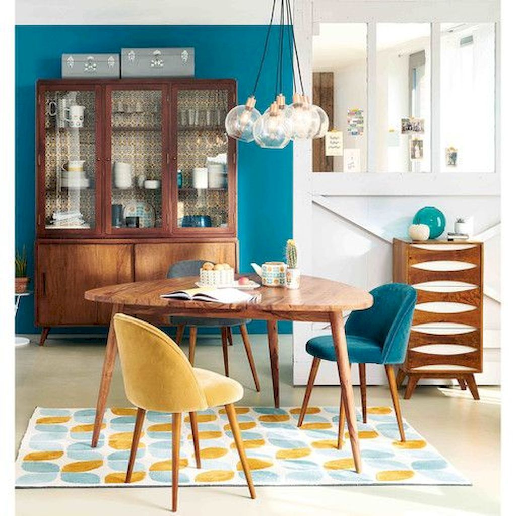 dining room, white wall, blue wall, wooden riangle table, blue velvet chairs, yellow velvet chair, glass pendant, blue yellows rug