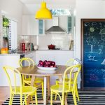 Dining Room, Woode Floor, Black White Striped Rug, White Kitchen Cabinet, White Wall, Round Table, Yellow Chairs, Yellow Pendant