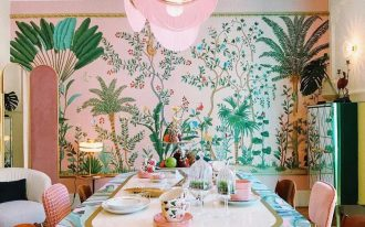 dining room, wooden floor, pink wallpaper with plants, pink cream chairs, green chair, white chair, white pendants with pink fringes, mirror ceiling