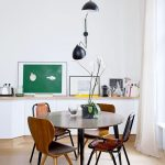 Dining Room, Wooden Floor, White Wall, Black Sconces, White Cabinet, Brown Round Table, Brown Chairs