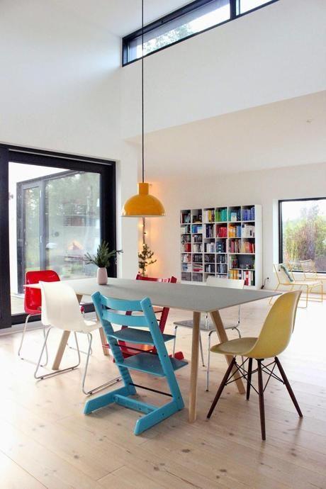 dining room, wooden floor, white wall, white bookshelves, wooden dining table, modern chairs, orange pendant, big glass window