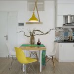 Dining Room, Wooden Floor, White Wall, White Kitchen Cabinet, Patterned Backsplash, Wooden Dining Table, White Yellow Modern Chair, Yellow Pendant